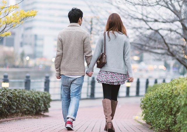 手を繋いで仲良く買い物に行くカップルの後ろ姿