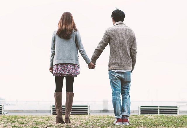 目的地についた手を繋いでラブラブなカップルの後ろ姿