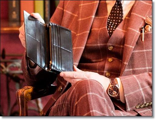 ココマイスターのシェルコードバン長財布を眺めているダンディなおっさん